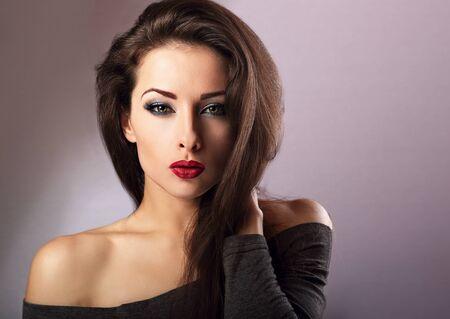 red lips: La mujer atractiva hermosa maquillaje con lápiz labial rojo caliente y los ojos largo latigazos Expresión de mirada sobre fondo azul Foto de archivo