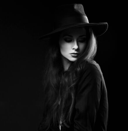 hair and beauty: Expressive female makeup model posing in black shirt and elegant hat on dark background and with thinking look looking down. Dramatic light. Black and white