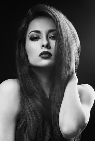 Beautiful makeup glamour female model with red lipstick and long eyelashes looking sexy on dark background. Closeup portrait. Black and white. Art