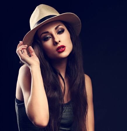 smoky black: Beautiful cool female model with long hair posing in cowboy summer hat and fashion top on dark background. Closeup portrait Stock Photo