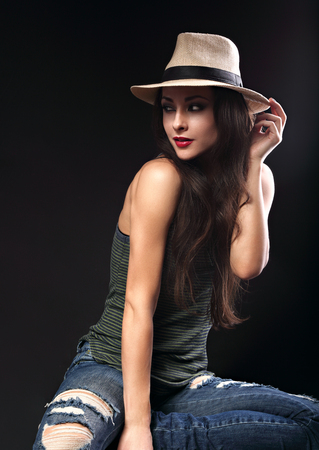 sexy female: Beautiful sexy female model with holding the hand cowboy summer hat and posing in fashion top and ripped jeans on dark background
