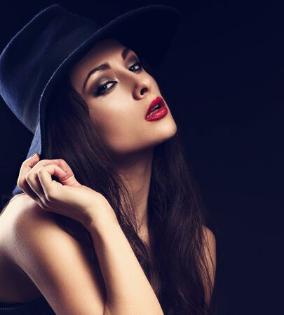 red lips: Beautiful cool female model with long hair posing in blue fashion hat and bright red lipstick on dark background. Closeup portrait Foto de archivo