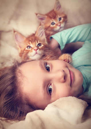 cute kittens: Beautiful happy kid girl lying with cute two maine coon kittens and looking fun. Closeup toned soft tender portrait