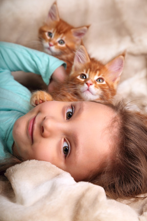 cute kittens: Beautiful happy kid girl lying with cute two maine coon kittens and looking fun. Closeup portrait