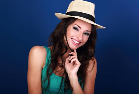 women smiling: Natural expression smiling beautiful woman in straw summer hat with long curly hair style looking on blue background. Closeup bright portrait