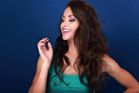 natural looking: Natural laughing beautiful emotional curly long hair style woman looking with hand near the face on bright blue background Stock Photo
