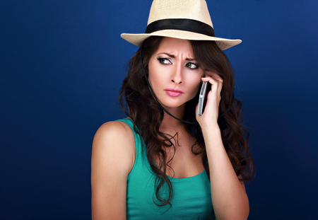 Gloomy unhappy frustration woman in summer hat talking on mobile phone and listening the bad news with angry look on blue background