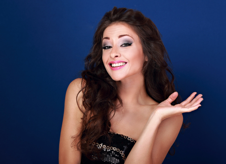 Excited beautiful makeup woman grimacing and showing oops sign her hand on blue background. Closeup portrait