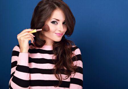 visagiste: Beautiful makeup happy woman holding and advertising make-up powder brush on blue background. Happy visagiste professional female Stock Photo