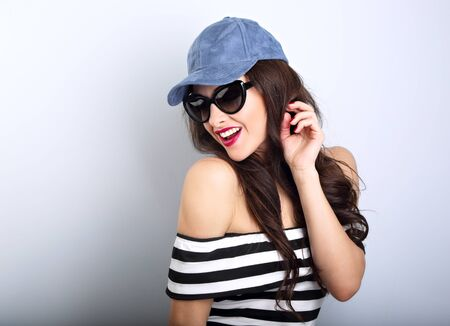 happy woman: Happy enjoyment young woman in sun glasses and blue cap posing and looking down posing in striped clothing. Closeup portrait Stock Photo
