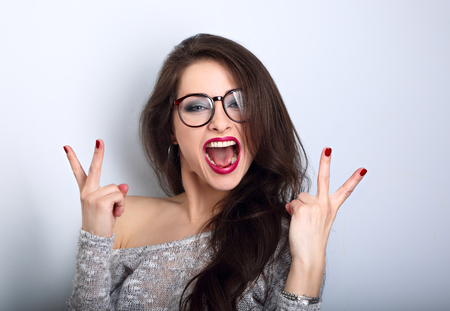 Young happy female woman in glasses with open wide mouth showing rock v-sigh gesture on blue background with empty copy space. Bright makeup Фото со стока