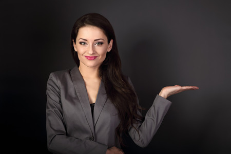 Beautiful smiling business woman in suit holding and presenting something empty on the hand on dark grey background
