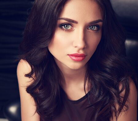 natural looking: Beautiful cute makeup woman with pink lipstick and long curly hair looking her big romantic blue eyes. Closeup toned portrait of natural emotion face Stock Photo