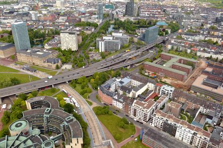 famous industries: High top view of long motorway and many roofes of city houses from Dusseldorf Rhine Tower in summer sunny day. Germany