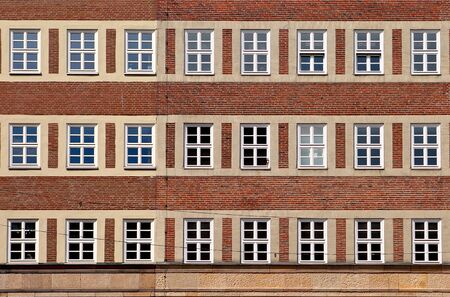 old building facade: Classic front flat house facade pattern from red brick with white window frame. Old vintage building. Germany