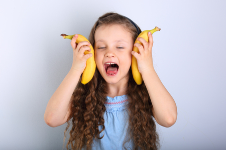 Playful happy fun long hair kid girl showing tongue and holding yellow bright bananas with closed eyes on blue background