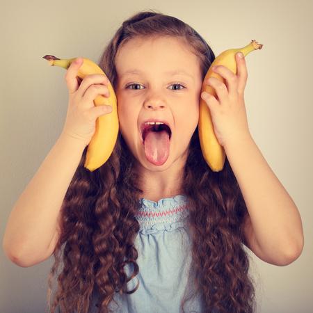 遊び心あふれる楽しみの長い髪の子供女の子舌と持株黄色きらきらバナナを示します。トーンのヴィンテージの肖像画 写真素材