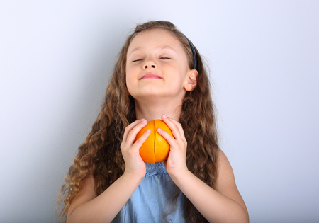 Cute smiling happy kid girl with curly hair style holding the hands the citrus orange fruit slices under with opened enjoying eyes on blue background