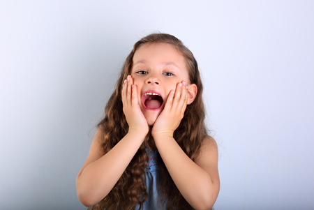 Excited surprising kid girl with wide open mouth and big eyes looking on empty copy space