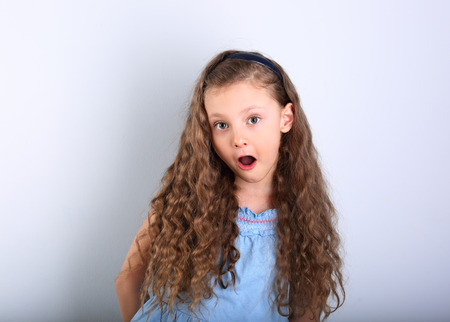Excited surprising kid girl with wide open mouth and big eyes looking on blue empty copy space background.