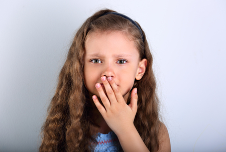 Unhappy afraid emotional small kid girl with teeth pain covering hand the mouth. Closeup portrait on blue background photo