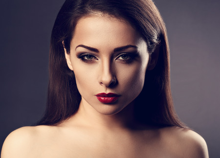 Beautiful vamp makeup sexy woman with hot red lipstick and long eye lashes looking expression on grey background in dramatic light. Closeup toned portrait Stock Photo