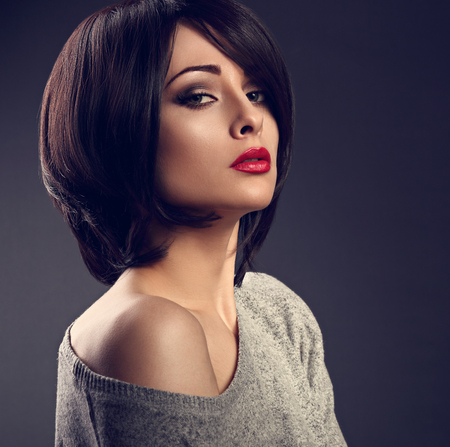 Beautiful makeup sexy woman with short hair style with hot red lipstick on dark shadow background. Closeup portrait. Toned photo