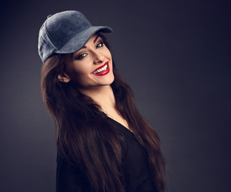 Happy toothy smiling beautiful brunette woman in baseball blue cap with long hair style in fashion black shirt looking on dark shadow background. Closeup portrait photo