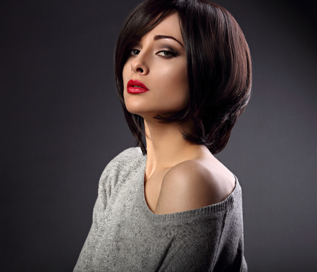 Beautiful makeup sexy woman with short hair style with hot red lipstick on dark shadow background. Closeup portrait photo