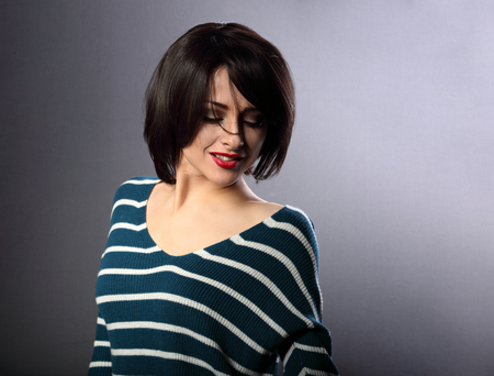 Beautiful enjoying smiling woman moving and shaking her short black hair style with red lipstick on grey background in fashion pullover photo