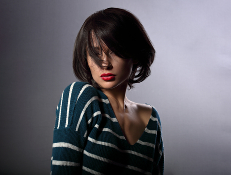 Beautiful enjoing woman moving and shaking her short black hair style with red lipstick on grey background in fashion pullover photo