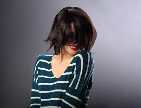 Beautiful smiling enjoing woman moving and shaking her short black hair style with red lipstick on grey background in fashion pullover photo