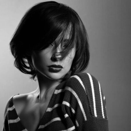 Beautiful enjoing woman moving and shaking her short black hair style in fashion pullover. Black and white. Art photo