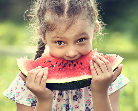 Beautiful kid girl eating big red watermelon with fun humor look on summer day green glass background. Closeup toned portrait photo