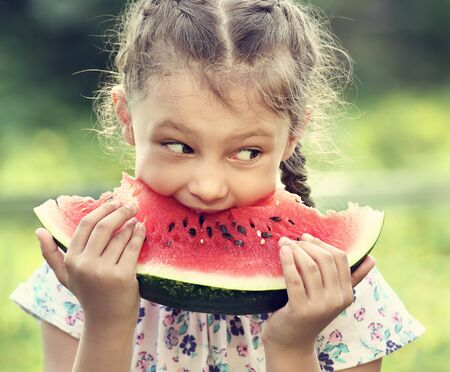 Beautiful kid girl eating big red watermelon on summer day green glass background. Closeup toned portrait photo