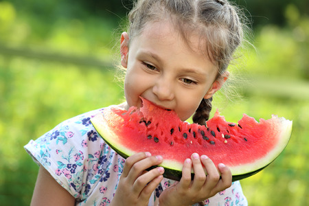 Beautiful kid girl eating big red watermelon with fun emotional look on summer day green glass background. Closeup portrait photo