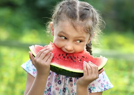 Beautiful kid girl eating big red watermelon on summer day green glass background. Closeup potrait photo