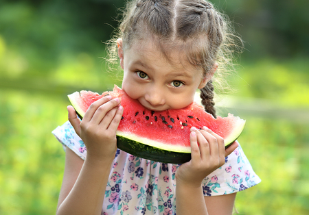 Beautiful kid girl eating big red watermelon with fun humor look on summer day green glass background. Closeup potrait photo