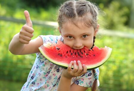 Beautiful kid girl eating big red watermelon with fun humor look and showing thumb up on summer day green glass background. Closeup potrait photo