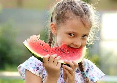 Beautiful kid girl eating big red watermelon with fun look on summer day green glass background. Closeup fun cute potrait photo