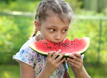 Beautiful kid girl eating big red watermelon with fun look on summer day green glass background. Closeup potrait photo