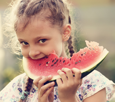 Beautiful kid girl eating big red watermelon with fun look on summer day green glass background. Closeup fun cute potrait. Toned photo