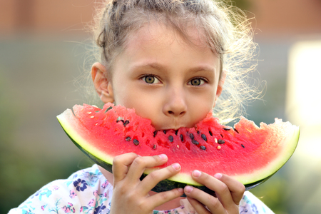 Beautiful kid girl eating big red tasty watermelon with cute look on summer day green glass background. Closeup fun potrait. photo