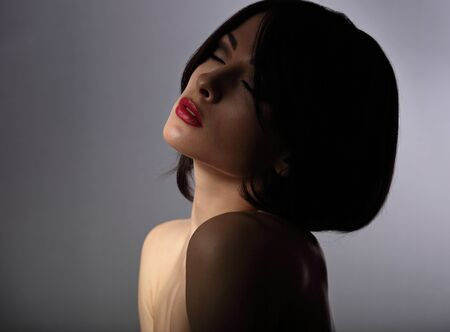 Sexy beautiful makeup woman with short hair style, red lipstick on dark shadow background with closed eyes. Closeup portrait. photo