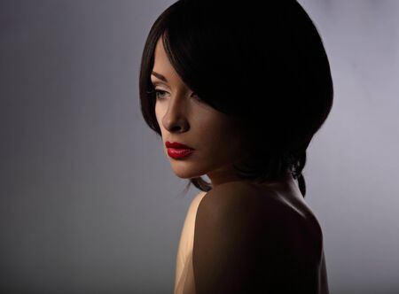 Beautiful makeup woman with thinking sad look and short hair style, red lipstick on dark shadow background. Closeup portrait photo