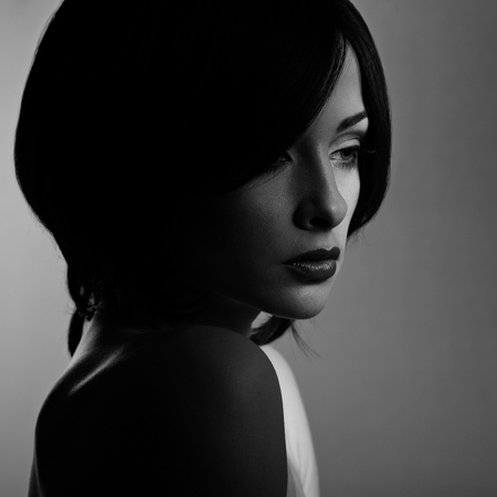 Beautiful makeup woman with thinking sad look and short hair style, red lipstick on dark shadow background. Closeup portrait? Black and white photo