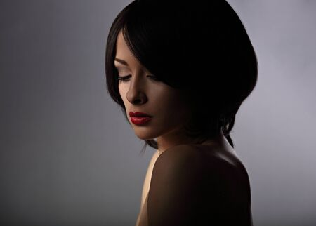 Beautiful makeup woman with thinking sad looking down and short hair style, red lipstick on dark shadow background. Closeup portrait photo