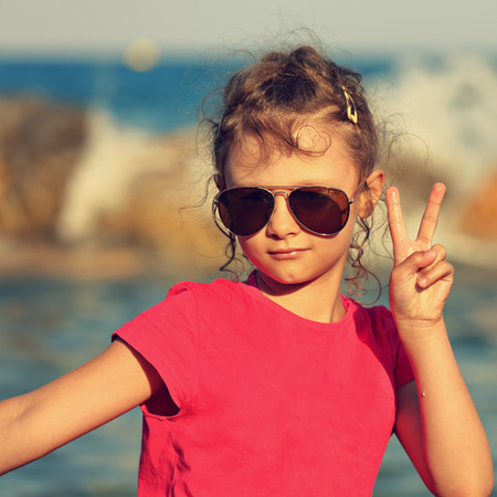 Cute beautiful kid girl in fashion sunglasses showing v sign making the selfie on blue sea and sky background. Toned closeup portrait
