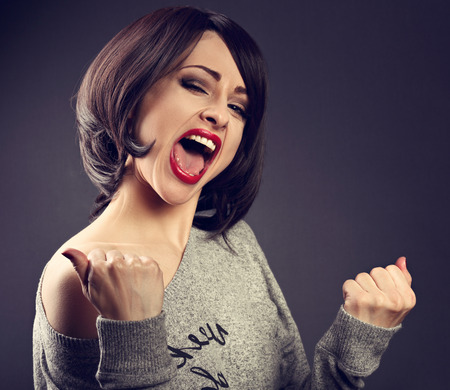 Excited winner makeup short hair style woman with opened mouth. Happy young satisfacted female showing the gesture yes by fists on grey dark background. Closeup toned portrait