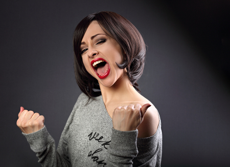 Excited winner makeup short hair style woman with opened mouth. Happy young satisfacted female showing the gesture yes by fists on grey dark background